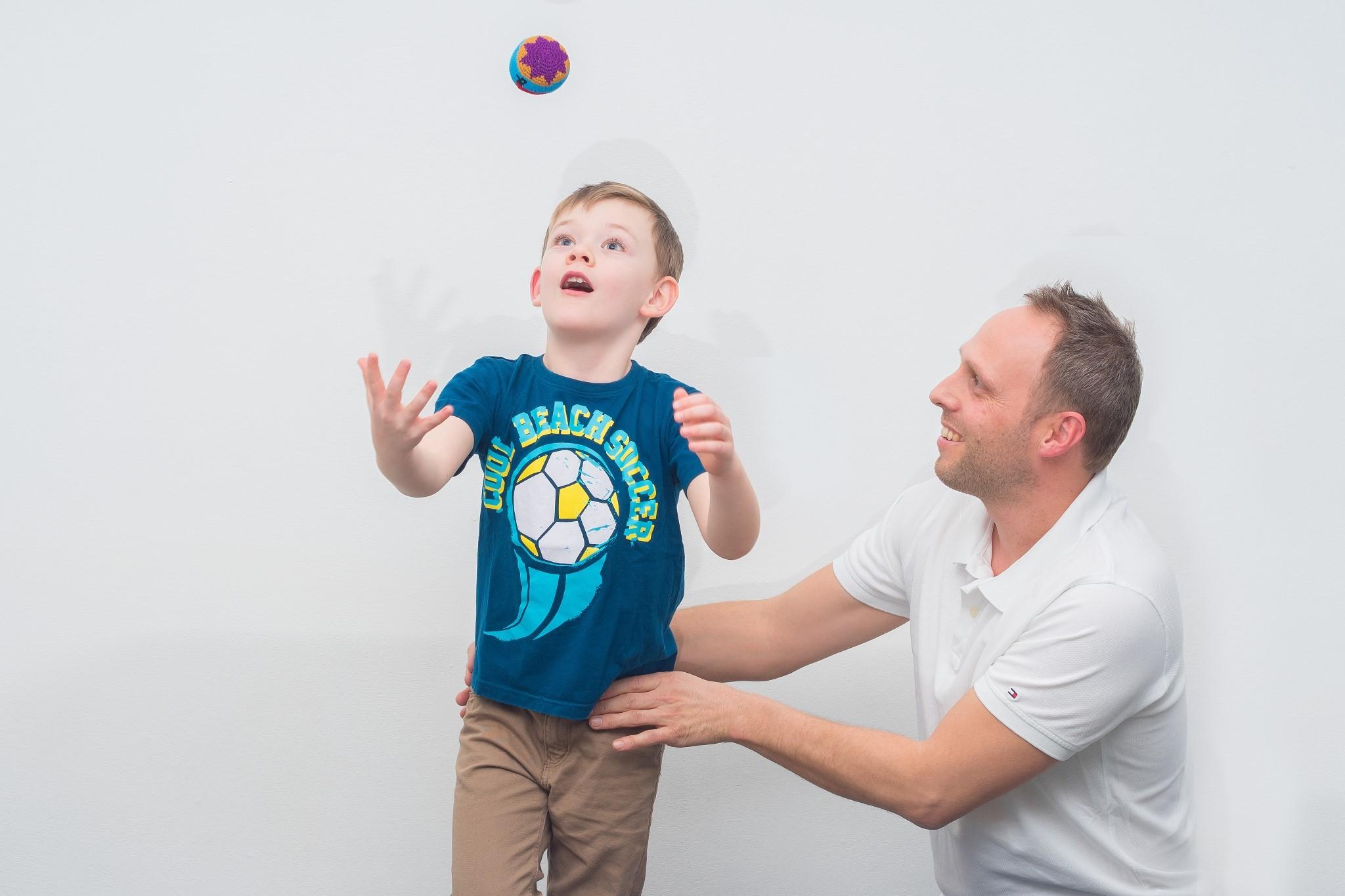 Ergotherapie mit Kindern - Kind fängt Ball auf einem Bein